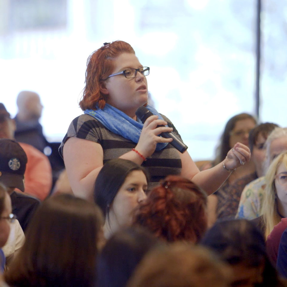 Woman asking question at a Partner Open Forum